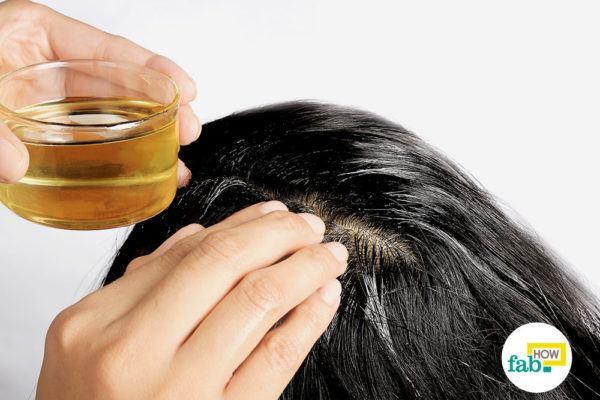 गुनगुने नारियल तेल को बालों की जड़ों में लगाइए