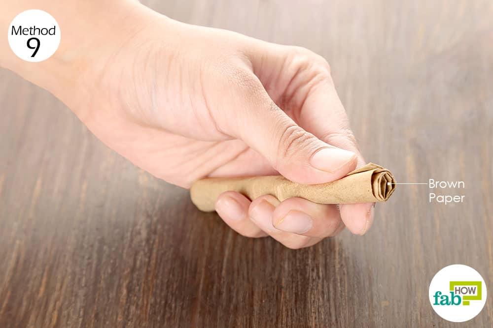 मसूड़ों और ऊपर के होंठ के बीच में भूरे रंग का कागज रखिये